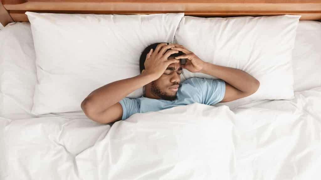 Restless african american man waking up with headache