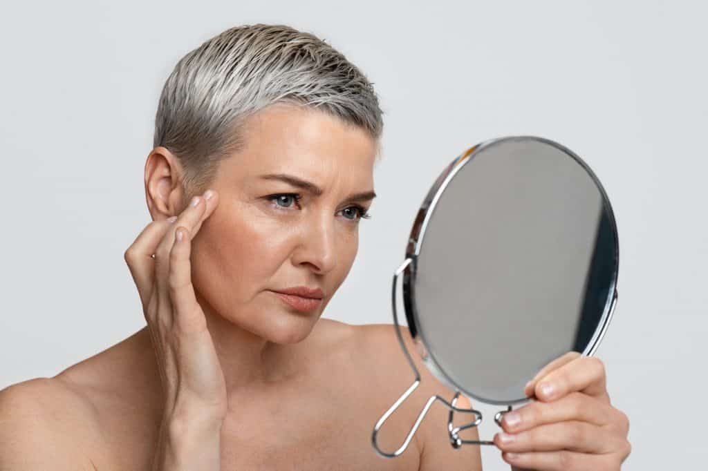 Skin Aging. Mature woman looking in the mirror checking her wrinkles