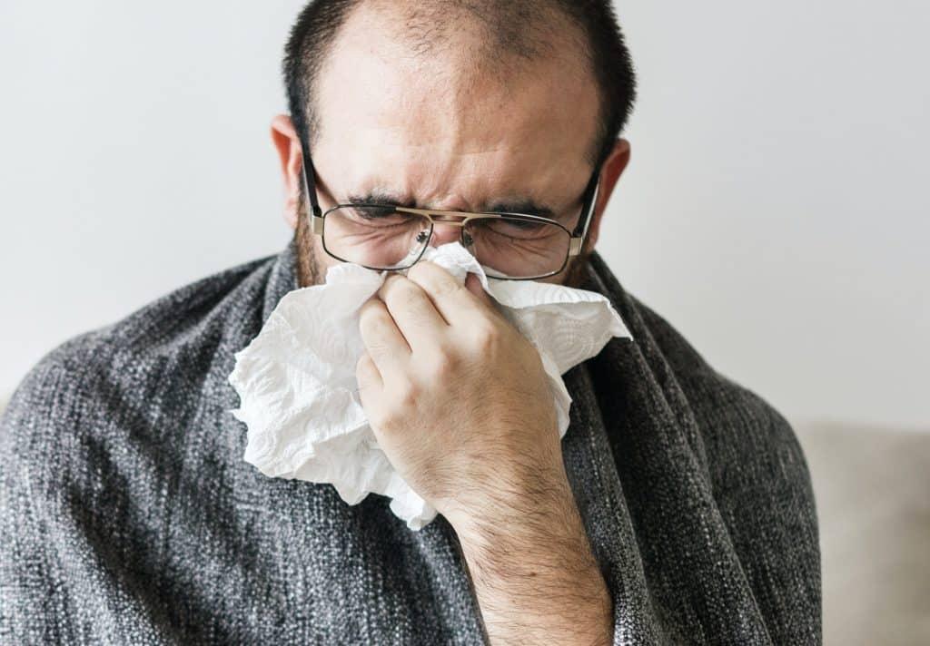 Man sneezing into tissue paper